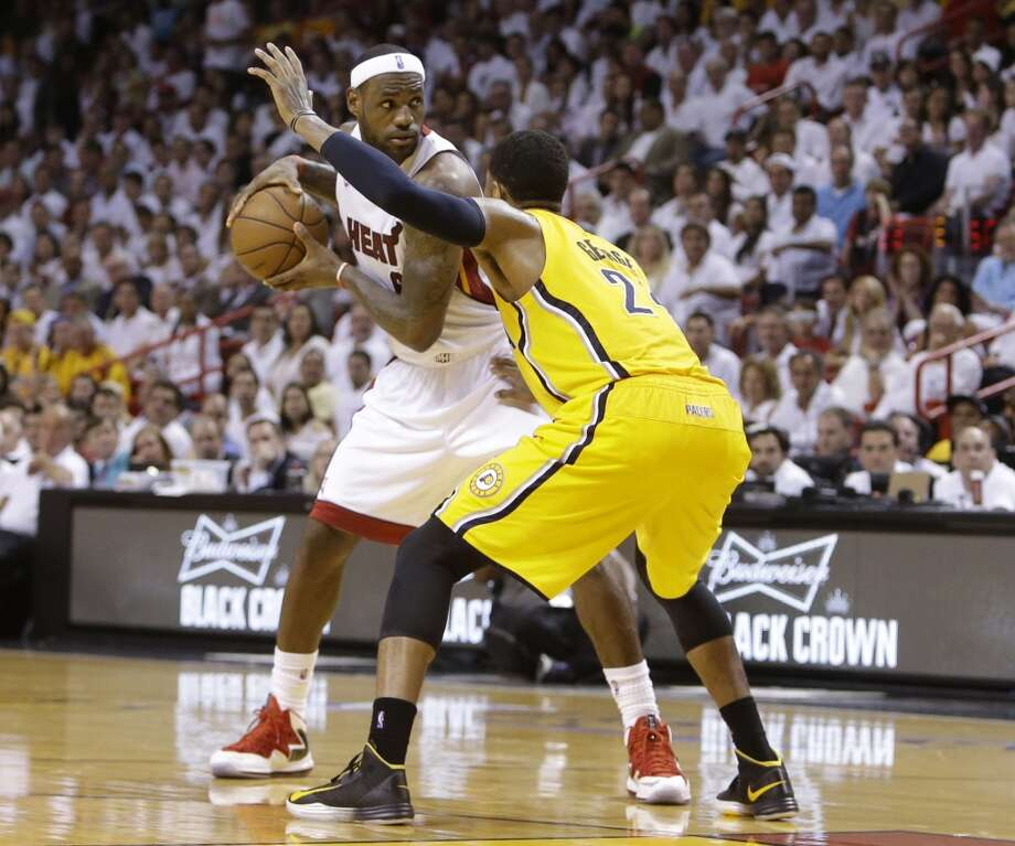 Miami Heat  forward LeBron James (6) looks to pass as Indiana Pacers small forward Paul George (24) defends during the second half of Game 7 in their NBA basketball Eastern Conference finals playoff series, Monday, June 3, 2013 in Miami. (AP Photo/Lynne Sladky)