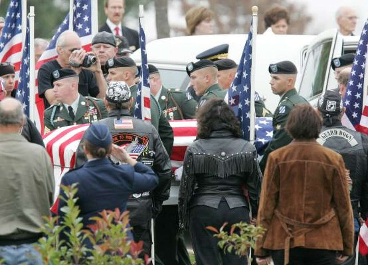 An honor guard carries the coffin of Army Spc. Jason Dean Hunt in Norman, Okla., on Nov. 14.
