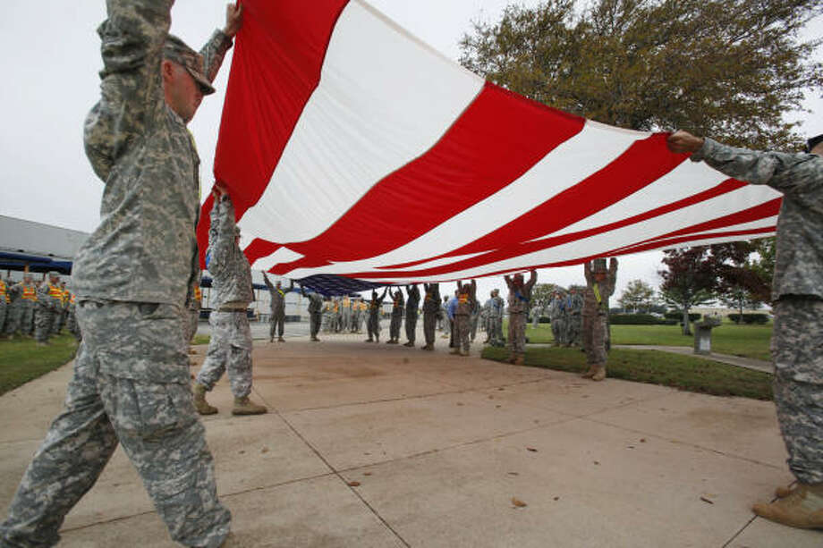 Soldiers from Fort Hood fold an American flag Monday in preparation for President Obama's planned visit on Tuesday. Photo: Paul Sakuma, Associated Press