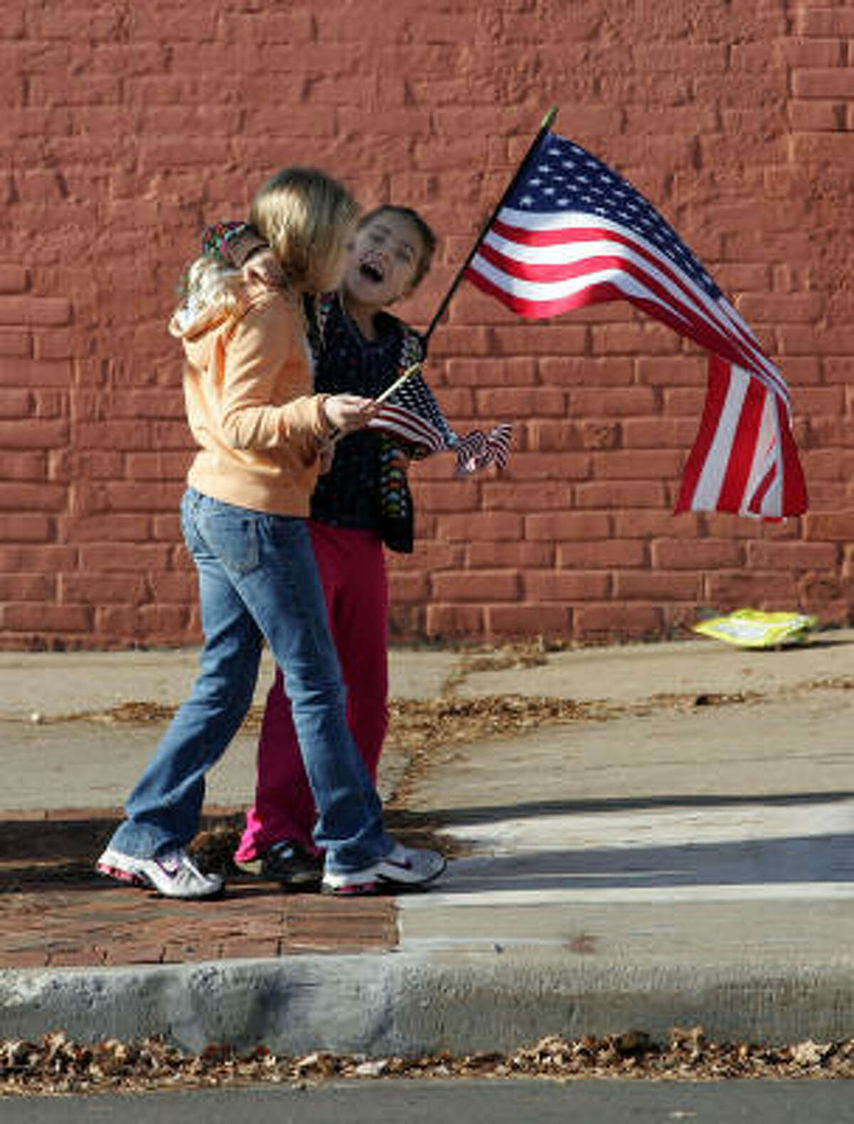 Bethany Hayden, left, 8, and Lennon Richie, 7, clutch their American flags as they line up in Plymouth for DeCrow's funeral procession.