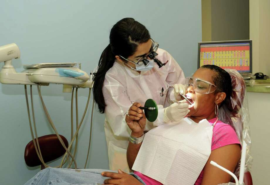 Dr. Sepideh Shirali work on Mary Cannon's teeth at the Good Neighbor Healthcare Center in the Heights. Photo: George Wong