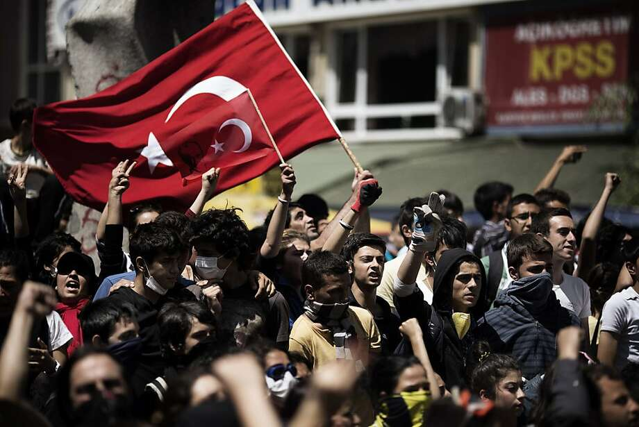 """Turkish demonstrators hold their national flag on June 4, 2013 during a protest in front of the prime minister's office in Ankara. Turkey's Islamic-rooted government said on June 4 it had """"learned its lesson"""" and appealed for an end to mass street protests that have convulsed the country for days in the worst political crisis in a decade. Photo: Marco Longari, AFP/Getty Images"""