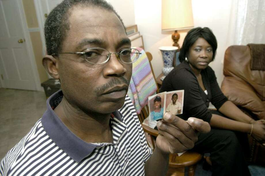 Emmanuel Maxi, holds photos of his nieces and nephews in Haiti. He and his wife Margarette,of Danbury, are both from Haiti and have many family members still there. Photo: Carol Kaliff / The News-Times