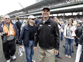 San Francisco 49ers head football coach Jim Harbaugh, who drove the pace car to start the Indianapolis 500 auto race, walks through the pit area before the start of the race at the Indianapolis Motor Speedway in Indianapolis  Sunday, May 26, 2013.