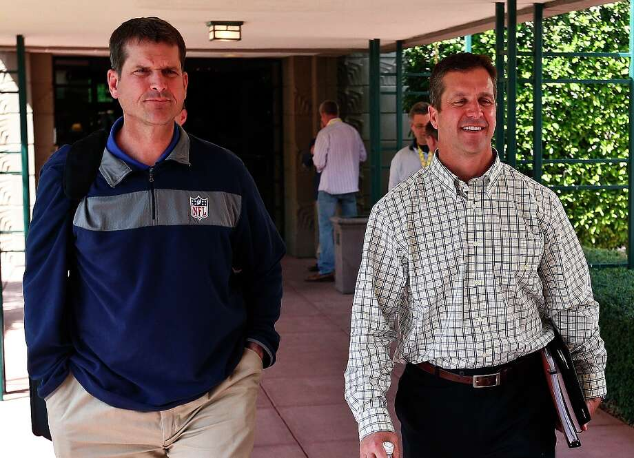 San Francisco 49ers coach Jim Harbaugh, left, walks with his brother John Harbaugh, coach of the Baltimore Ravens, at the NFL football annual meetings Tuesday, March 19, 2013, in Phoenix. Photo: Ross D. Franklin, Associated Press / AP