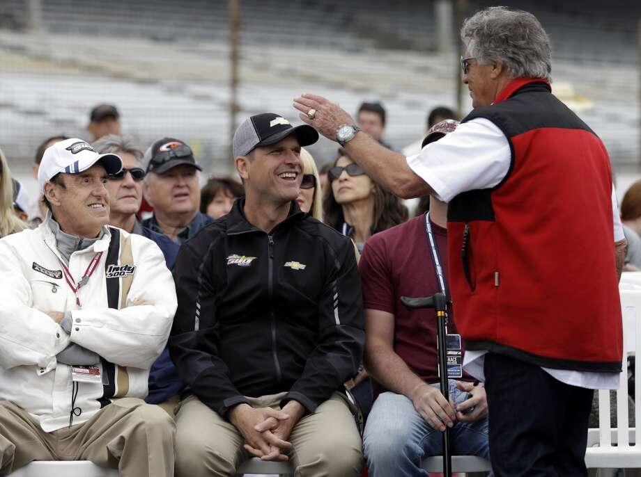 1969 Indy 500 champion Mario Andretti, right, talks with San Francisco 49ers head football coach Jim Harbaugh, center, and entertainer Jim Nabors during the public drivers meeting for the Indianapolis 500 auto race at the Indianapolis Motor Speedway in Indianapolis, Saturday, May 25, 2013. Photo: Darron Cummings, Associated Press
