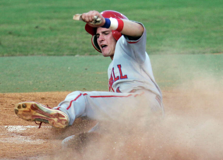Tomball's Anthony Lucas slid safely into home plate against Foster in the Cougars' 10-0 win in the Region III-4A title game. The Cougars now move on and will face Wichita Falls Rider in the UIL Class 4A State Baseball Tournament in Round Rock Friday. Photo: Melissa Phillip, Staff / © 2013  Houston Chronicle