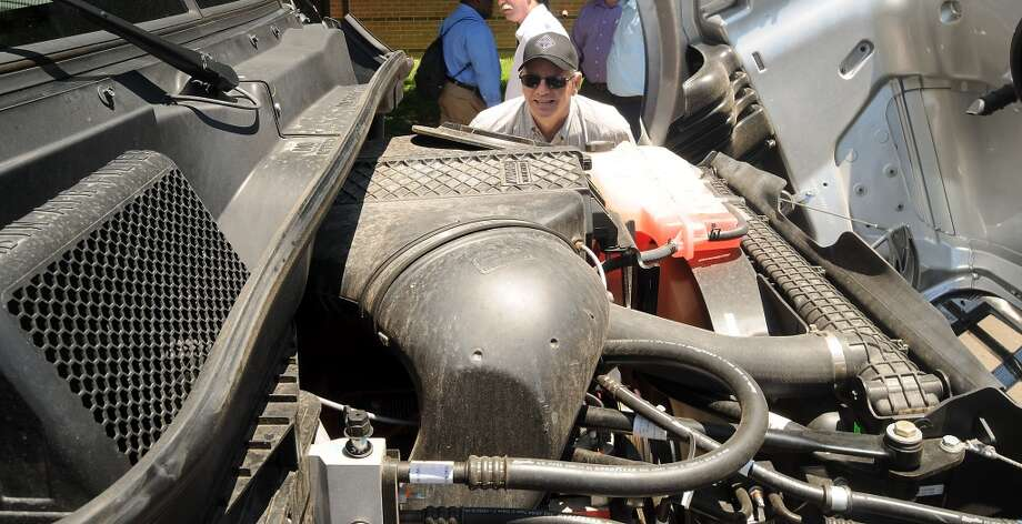 Mike Lewis of DPC Industries looks at the engine of a natural gas-powerd Ryder Truck at Minute Maid Park Tuesday June 04, 2013. Photo: Dave Rossman, For The Houston Chronicle