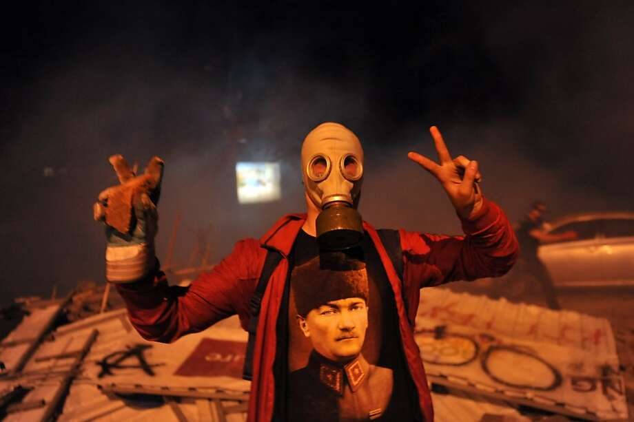 A gas-masked protester flashes V-signs during clashes over a development project near Istanbul's iconic Taksim Square. Demonstrations against the project have snowballed into widespread anger against what critics say is the government's increasingly conservative and authoritarian agenda. Photo: Ozan Kose, AFP/Getty Images