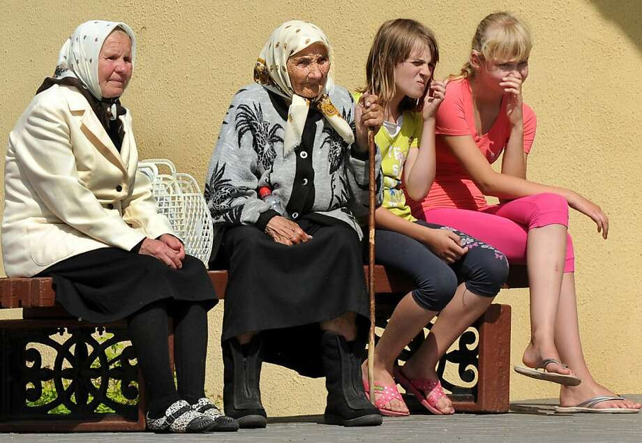 Across generations: Elderly women and teenage girls share a bench to watch a wedding party in the Belarus village of Lyaskovich. Photo: Viktor Drachev, AFP/Getty Images