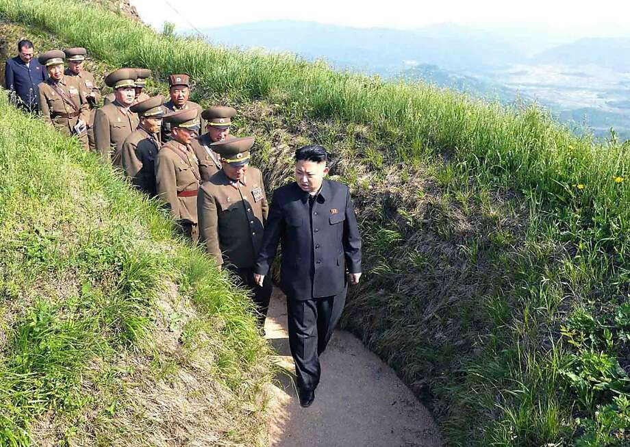 Followed by an entourageof sycophants officers, North Korean leader Kim Jong-Un inspects watch posts defending Mt. Osong and Korean People's Army unit 507 in the Kangwon province. Photo: Kns, AFP/Getty Images