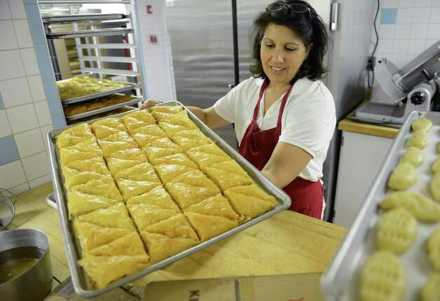 Tina Delasos, of Brookfield, handles a tray of fresh-baked baklava in preparation for the festival, The Greek Experience, at the Assumption Greek Orthodox Church in Danbury, Conn. on Tuesday, June 4, 2013.  The festival runs Friday through Sunday and will have traditional Greek food, Greek dancing, raffles, games and other activities. Photo: Tyler Sizemore / The News-Times
