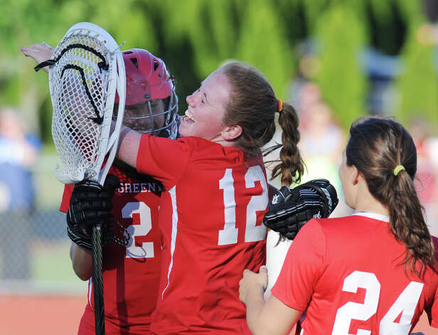 At center, Emily Bacon (# 12) of Greenwich hugs teammate and goalie Kylie Ginsberg, left, after Greenwich defeated Gl