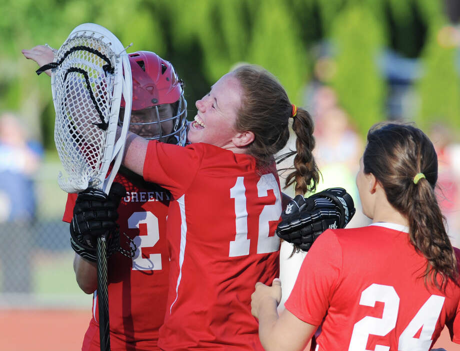 At center, Emily Bacon (# 12) of Greenwich hugs teammate and goalie Kylie Ginsberg, left, after Greenwich defeated Glastonbury in the Class L girls lacrosse semifinal match between Greenwich High School and Glastonbury High School at Cheshire High School, Tuesday evening, June 4, 2013. At right closing in to join the celebration is Elizabeth Trotta (# 24) of Greenwich. Greenwich advanced to the final, defeating Glastonbury, 11-8 Photo: Bob Luckey / Greenwich Time