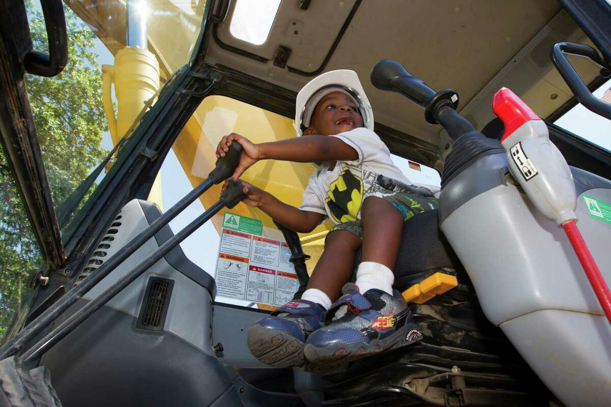 Prince Edward Ford, 2, sits inside an excavator Tuesday as the city of Houston began demolishing 63 vacant units to make way for an $800,000 community park at the Kelly Village Apartments in the Fifth Ward.