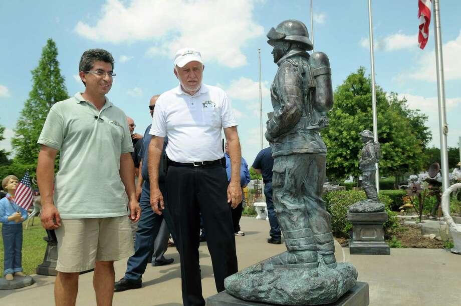 Fernando Gomez, from left, and Billy Frazier, co-owners of Frazier's Ornamental & Architectural Concrete in Hempstead, check the two commeremorative statues donated to the Houston Fire Department in honor of the firefighters lost in last Friday's blaze at Southwest inn. Photo: Jerry Baker, For The Chronicle