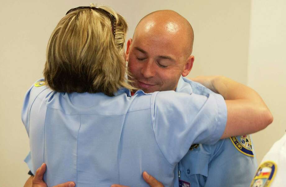 Houston Fire Capt. Michael Mire gets a supportive hug at the conclusion of an HFD command staff meeting Tuesday. Mire, 37, joined the department in 2002, and has served as its family assistance coordinator for the past eight years. Photo: J. Patric Schneider, Freelance / © 2013 Houston Chronicle