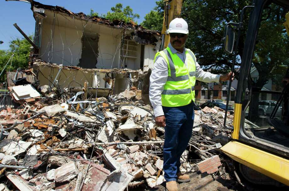 Environmental Contractor Inc. employee Jose Cardona helps the Houston Housing Authority on demolishing a vacant building at the Kelly Village Apartments in the Fifth Ward on Tuesday, June 4, 2013, in Houston.  Sixty-three vacant units were demolished to make way for a new community park. Photo: J. Patric Schneider, For The Chronicle / © 2013 Houston Chronicle