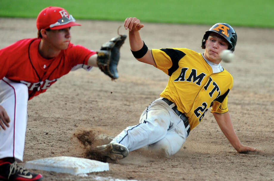 Amity's Sebastian DiMauro slides into third base in a steal attempt as Fairfield Prep's David Gerics receives the ball, during Class LL Semifinal baseball action in Bristol, Conn. on Tuesday June 5, 2013. DiMauro was called safe. Photo: Christian Abraham / Connecticut Post
