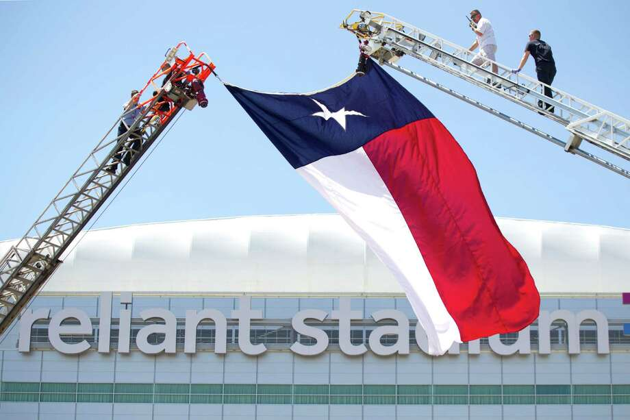 Houston firefighters raise a Texas flag outside Reliant Stadium. The public memorial service will be on Wednesday, starting at 10 a.m. Photo: Brett Coomer, Houston Chronicle / © 2013 Houston Chronicle