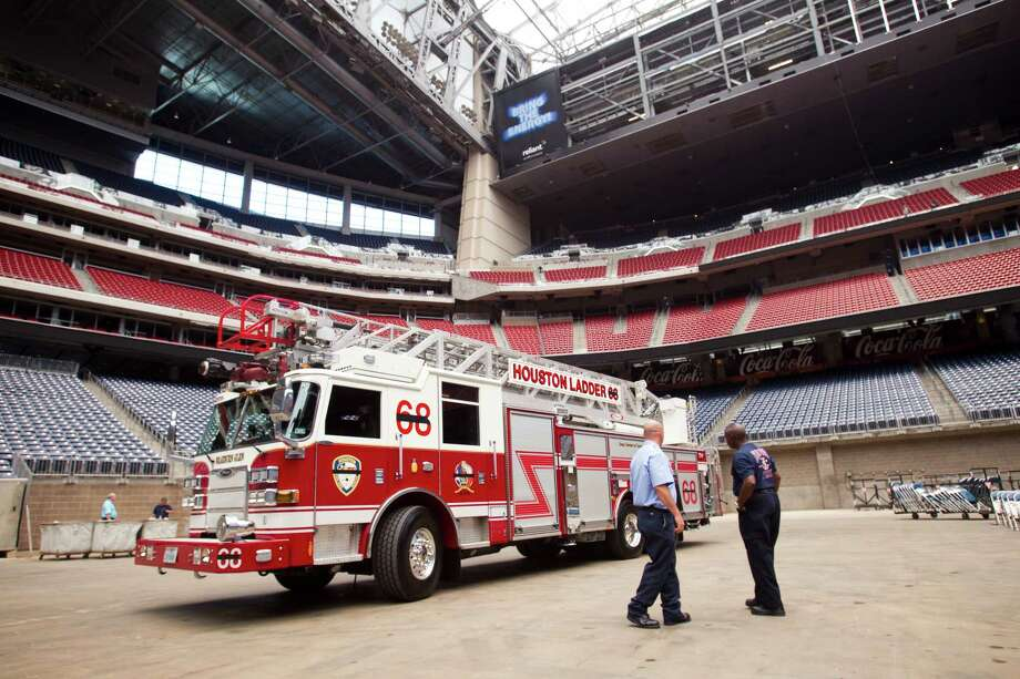 Houston Fire Department ladder 68 is placed inside Reliant Stadium during preparations for a memorial service for four fallen HPD firefighters Tuesday, June 4, 2013, in Houston. Photo: Brett Coomer, Houston Chronicle / © 2013 Houston Chronicle