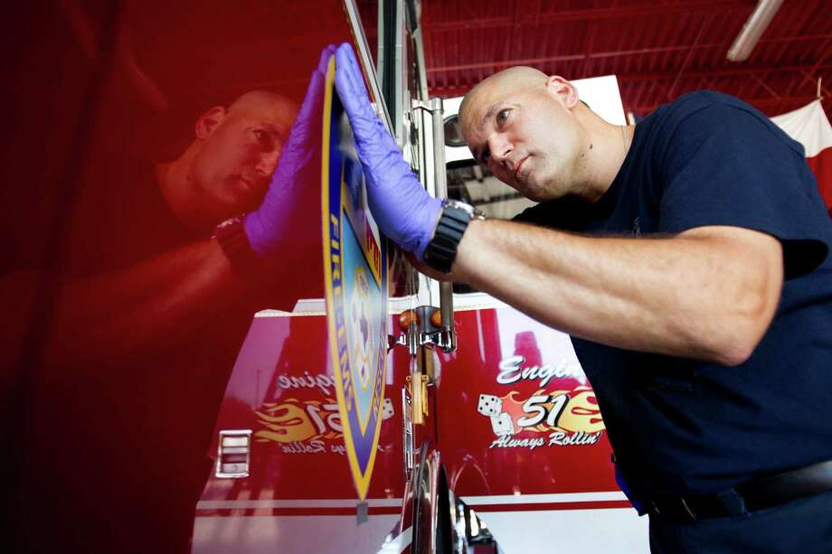 Houston firefighter Matt Opiela replaces a Houston Fire Department logo on the side of HFD Engine 51 while preparing the truck for a memorial service for four fallen HPD firefighters Tuesday, June 4, 2013, in Houston. Photo: Brett Coomer, Houston Chronicle / © 2013 Houston Chronicle