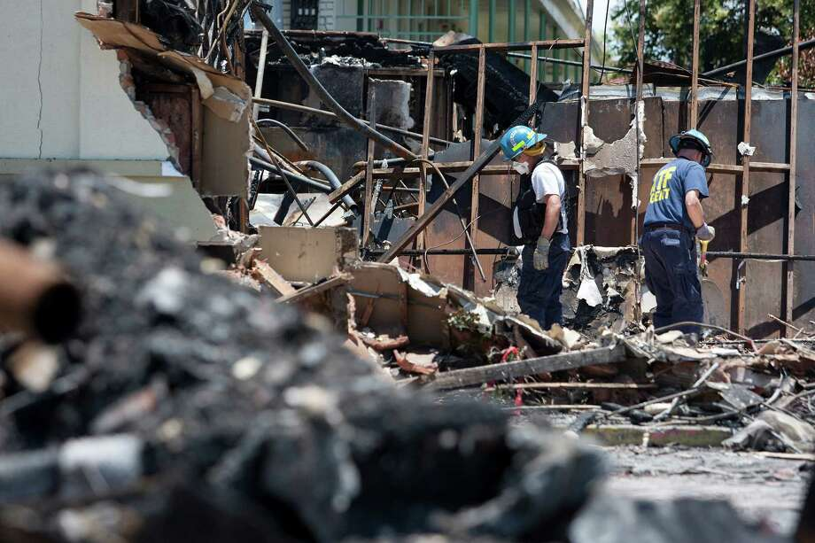 ATF agents, fire marshals and investigators continued to go through the burnt remains of the Southwest Inn and the Bhojan Indian restaurant on the 5800 block of the Southwest Freeway Tuesday, June 4, 2013, in Houston. Photo: Johnny Hanson, Houston Chronicle / © 2013  Houston Chronicle