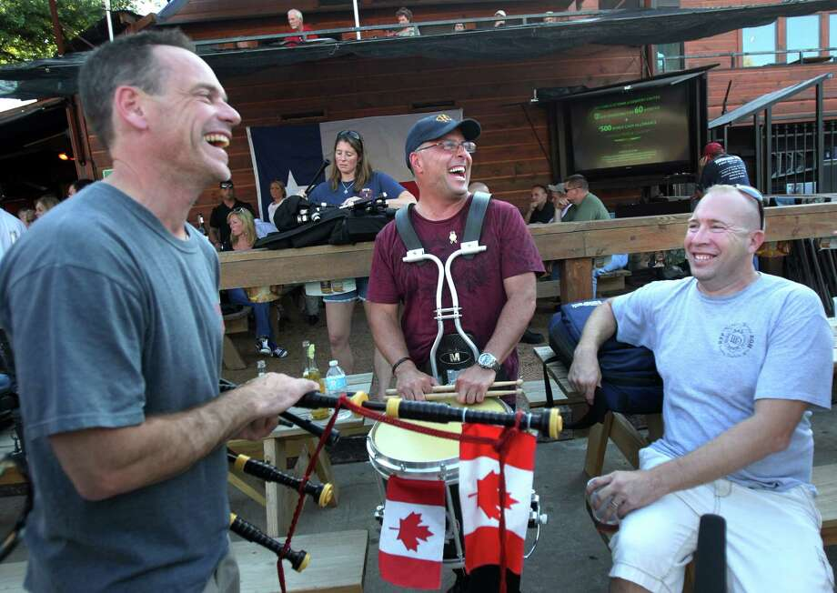 Bagpipers Rob Zimich and Paul Aziz, from Canada, share a laugh with Round Rock Firefighter Bill Clifton as they wait to practice at Hefley's Bar for Wednesday's firefighter memorial at Reliant on Tuesday, June 4, 2013, in Houston. Photo: Mayra Beltran / © 2013 Houston Chronicle