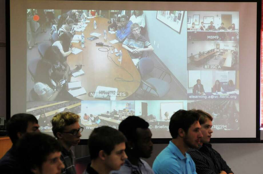 A large screen displays the video feed from various sites around the state during an event with New York State Education Commissioner John King, Jr., hosted by BOCES on Tuesday, June 4, 2013 in Colonie, NY.  High school students in journalism programs from around the state took part in person or  through a video conference feed and were able to ask questions of the commissioner.   (Paul Buckowski / Times Union) Photo: Paul Buckowski