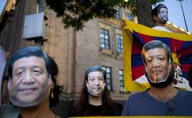 Supporters of a free Tibet wear masks of China's President Xi Jinping and hold a Tibetan flag to protest Xi's visit outside the National Palace where he is attending a dinner in Mexico City, Tuesday, June 4, 2013. Xi is in Mexico for a three day visit. (AP Photo/Eduardo Verdugo)