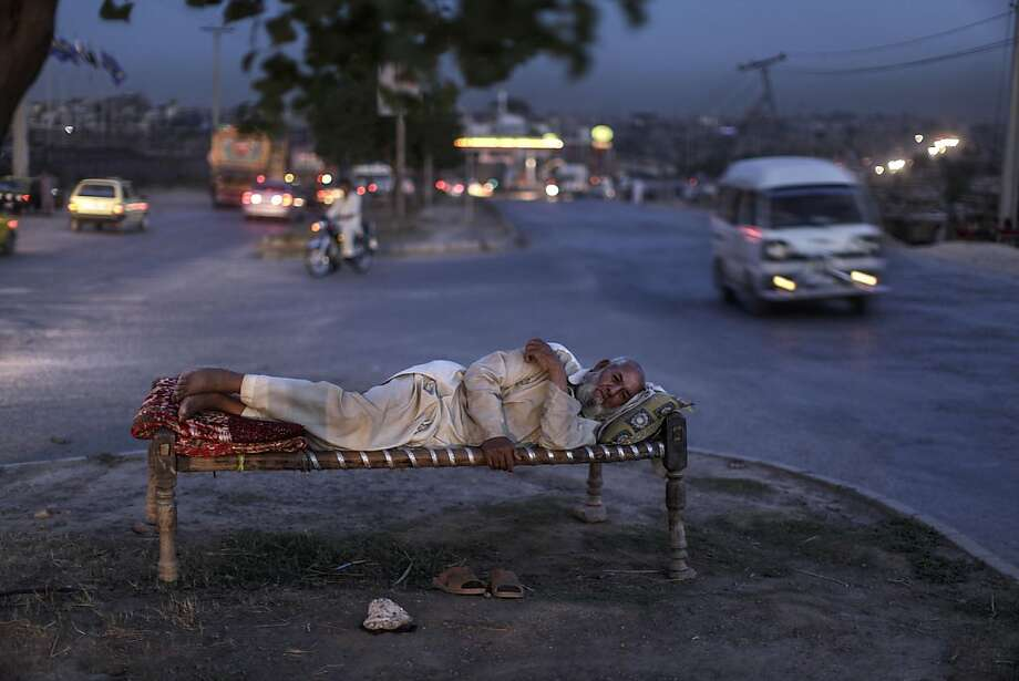 Crashing in the intersection: Eighty-year-old Gul Badshah, who fled his home in Pakistan's tribal region of Mohmand Agency because of the fighting between the Taliban and the army, lies on a bed in a median outside Islamabad. As temperatures rise, many Pakistanis sleep outdoors to escape the oppressive heat trapped in their homes. Photo: Muhammed Muheisen, Associated Press