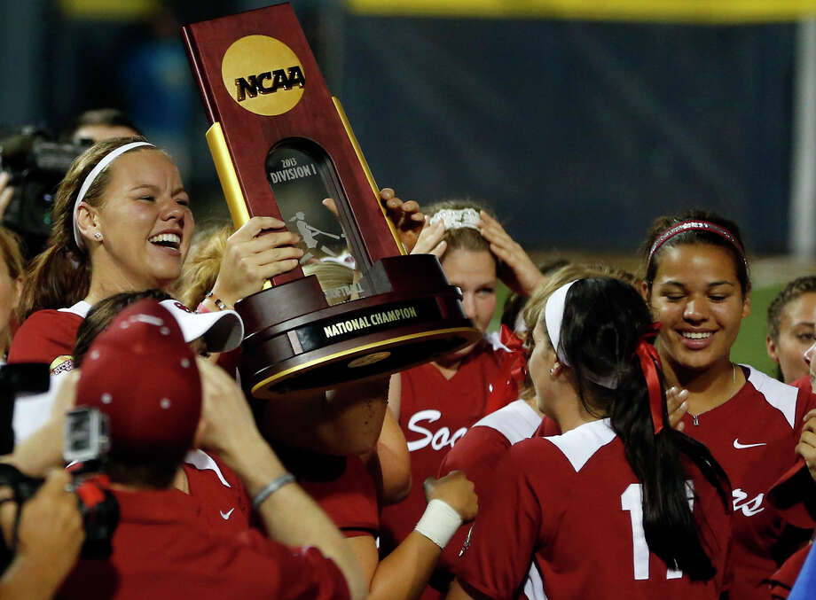 Keilani Ricketts, left, hoists the championship trophy after leading Oklahoma with her arm and bat. Photo: Sue Ogrocki, STF / AP