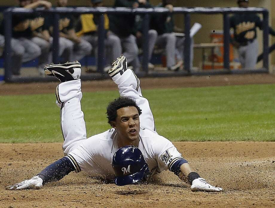 Milwaukee's Carlos Gomez slides home with the winning run on Yuniesky Betancourt's double. Photo: Morry Gash, Associated Press