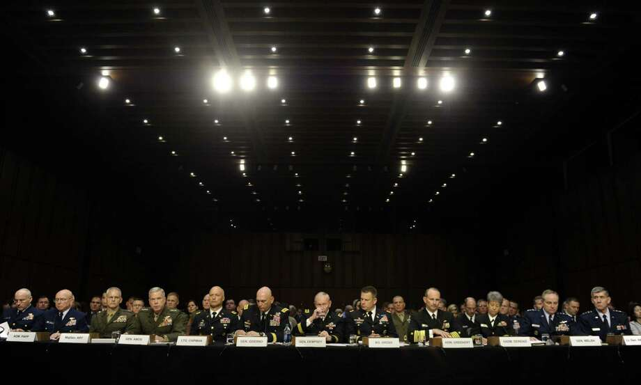 Gen. Martin Dempsey, the Joint Chiefs of Staff chairman (center), takes a drink of water as he and other top members of the nation's military leadership get ready to testify before a Senate Armed Services Committee on legislation regarding sexual assaults in the armed services. Photo: Susan Walsh / Associated Press