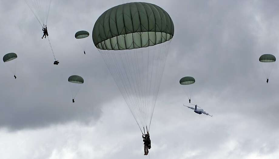 In this photo provided by the U.S. Army, the 4th Brigade Combat Team (Airborne), 25th Infantry Division continues Operation Spartan Reach, a mass tactical airborne training event across Alaska from Monday through Wednesday, with a parachute insertion into Malemute drop zone on Joint Base Elmendorf-Richardson, Tuesday, June 4, 2013. This is the largest airborne training mission in the history of the Spartan Brigade, dropping over 1,400 paratroopers, in addition to heavy equipment including two 105mm howitzers, at the Donnelly Drop Zone near Fort Greely, and JBER's Malemute Drop Zone using five C-17 Globemaster III aircraft, and one C-130 Hercules aircraft.  Operation Spartan Reach is designed to simulate a brigade-level airborne seizure of key terrain to enable the follow-on movement of forces into hostile territory. (AP Photo/U.S. Air Force, Justin Connaher) Photo: Justin Connaher, Associated Press