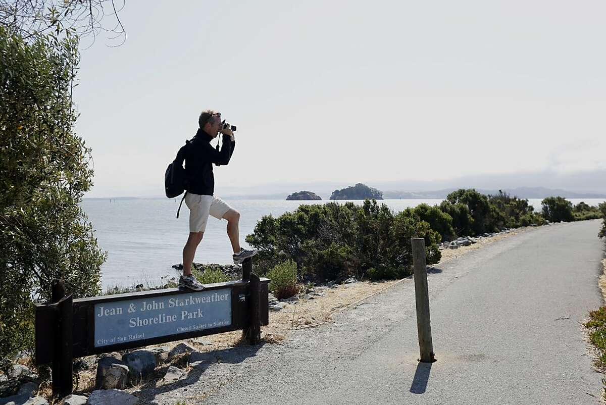 Kurt Schwabe takes pictures in San Rafael during a break on his hike on the Bay Trail.