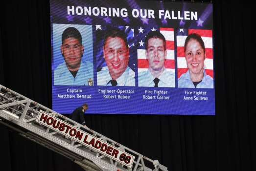 A firefighter walks down a ladder in front of a video board before a memorial service honoring four Houston firefighters at Reliant Stadium Wednesday, June 5, 2013. In Houston. Four firefighters died when a part of a building collapsed on them while they were searching for people they thought might be trapped inside a burning motel and restaurant last Friday. Photo: Houston Chronicle