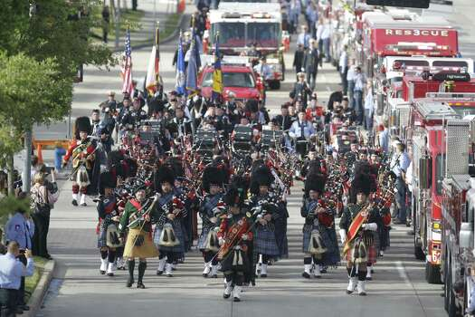Bagpipers lead The firefighters march along Kirby  to a memorial service honoring four Houston firefighters at Reliant Stadium Wednesday, June 5, 2013. Photo: Houston Chronicle