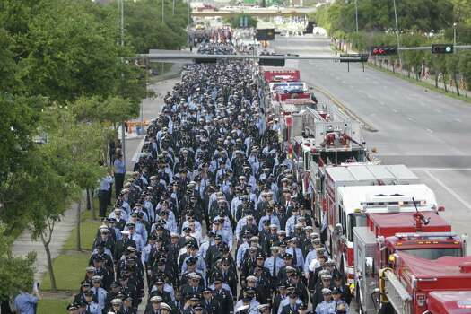 People watch from brudge as firefighters march along Kirby  to a memorial service honoring four Houston firefighters at Reliant Stadium Wednesday, June 5, 2013. Photo: Houston Chronicle