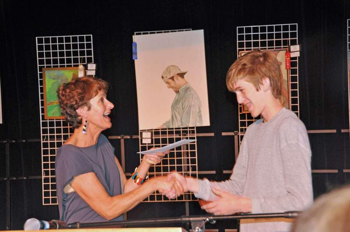 "Former Darien Arts Center President Lisa Thoren congratulates Darien High school student Graham Manning, who won first place for his photo ""Behind Closed Doors."""
