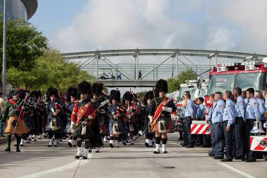Firefighter's from around Houston and Texas walk during a firefighter's memorial procession Wednesday, June 5, 2013 into Reliant Stadium.  As many as 40,000 people are expected to remember the four firefighters who died Friday, the deadliest day in the Houston Fire Department's 118-year history.   Killed in the fire when the motel structure collapsed were Capt. Matthew Renaud, 35,  engineer operator Robert Bebee, 41,  firefighter Robert Garner, 29, and Anne Sullivan, 24, a probationary firefighter who had graduated in April from the Houston Fire Department Academy.  (AP Photo / Michael Stravato) Photo: Michael Stravato, Associated Press / FR29619 AP