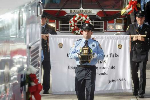 The helmets belonging to fallen firefighter, Anne Sullivan of Houston Firehouse 68, is carried during the memorial service honoring four Houston firefighters at Reliant Stadium Wednesday, June 5, 2013. In Houston. Four firefighters died when a part of a building collapsed on them while they were searching for people they thought might be trapped inside a burning motel and restaurant last Friday. Photo: Michael Paulsen, Houston Chronicle / © 2013 Houston Chronicle