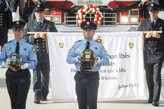 The helmets belonging to fallen firefighters, Robert Garner and Anne Sullivan of Houston Firehouse 68, are carried during the memorial service honoring four Houston firefighters at Reliant Stadium Wednesday, June 5, 2013. In Houston. Four firefighters died when a part of a building collapsed on them while they were searching for people they thought might be trapped inside a burning motel and restaurant last Friday. Photo: Michael Paulsen, Houston Chronicle / © 2013 Houston Chronicle