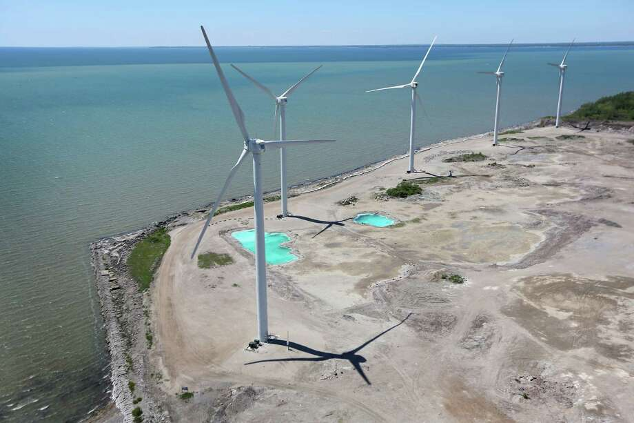 LACKAWANNA, NY - JUNE 04:  Wind Mills rise over Lake Erie on June 4, 2013 in Lackawanna, New York, near the U.S.-Canada border. The Steel Winds windmill farm, considered one of the largest urban renewable power developments in the world, is located on the grounds of the former Bethlehem Steel Plant. The aerial view was seen from a helicopter flown by the U.S. Office of Air and Marine, (OAM), which monitors and patrols the U.S.-Canada border. Photo: John Moore, Getty Images / 2013 Getty Images