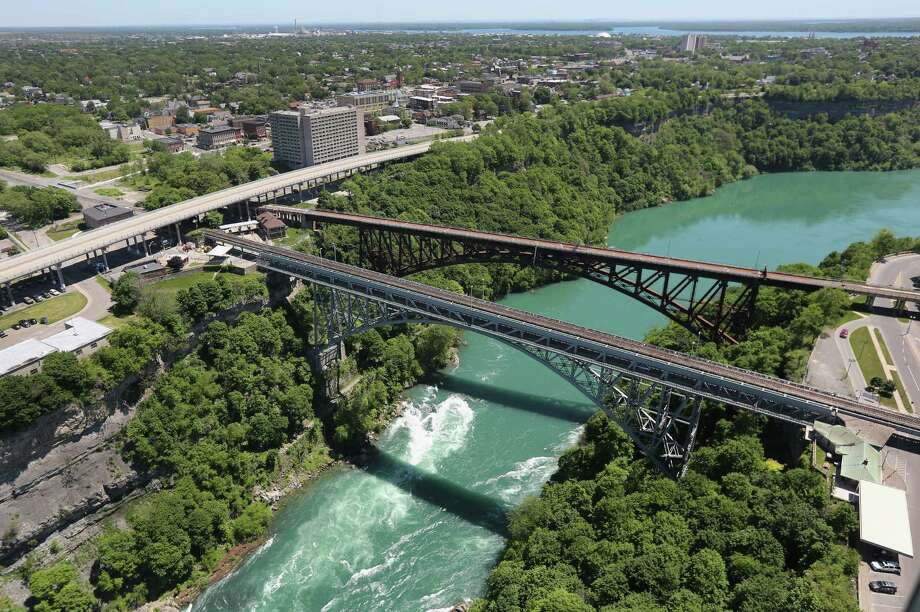 NIAGARA FALLS, NY - JUNE 04:  The Whirlpool Bridge crosses from the United States (L), into Canada over the Niagara River on June 4, 2013 at Niagara Falls, New York. The falls, which have a combined highest flow rate of any waterfalls in the world, stradle the U.S.-Canada border, on the the Niagara River, which drains Lake Erie into Lake Ontario. The falls, visited by millions of tourists on each side of the border, are also a major source of hydroelectric power for the region. The aerial view was seen from a helicopter flown by the U.S. Office of Air and Marine, (OAM), which monitors and patrols the U.S. northern border with Canana. Photo: John Moore, Getty Images / 2013 Getty Images