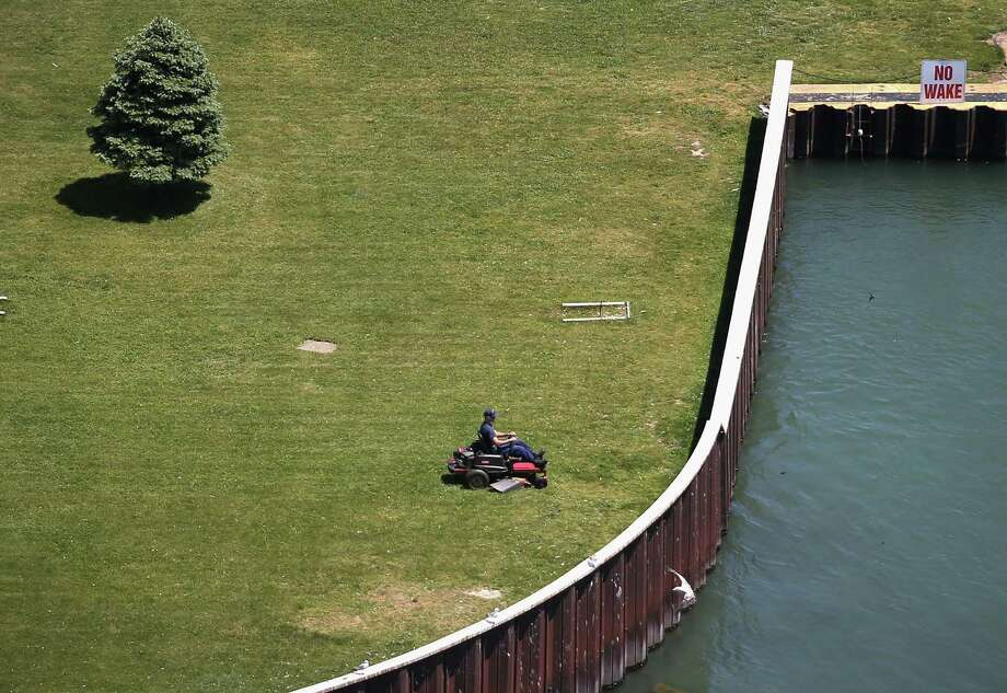 NIAGARA FALLS, NY - JUNE 04:  A worker cuts the grass at Fort Niagara at the mouth of the Niagara River into Lake Ontario on June 4, 2013 at Youngstown, New York. The river forms the border between the United States and Canada and drains Lake Erie into Lake Ontario. The river is a major source of hydroelectric power for the region. The aerial view was seen from a helicopter flown by the U.S. Office of Air and Marine, (OAM), which monitors and patrols the U.S. northern border with Canana. Photo: John Moore, Getty Images / 2013 Getty Images