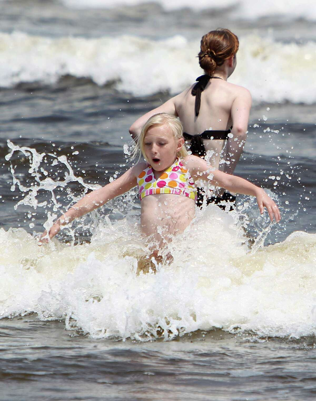 Betty Gallien, 8, of Huntsville, jumps into a wave as she joins her family on an early Memorial Day outing on Thursday, May 23, 2013, in Galveston. This Memorial Day weekend nearly 3 million Texans are expected to hit the roadways and pack airports according to AAA. ( Mayra Beltran / Houston Chronicle )