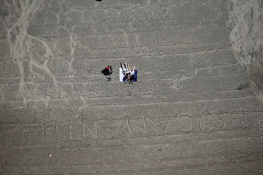 GRAND ISLAND, NY - JUNE 04:  A couple gets a headstart on summer while lying on a Niagara River beach on June 4, 2013 in Grand Island, New York, near the U.S.-Canada border. The aerial view was seen from a helicopter flown by the U.S. Office of Air and Marine, (OAM), which monitors and patrols the U.S. Canada border. Photo: John Moore, Getty Images / 2013 Getty Images