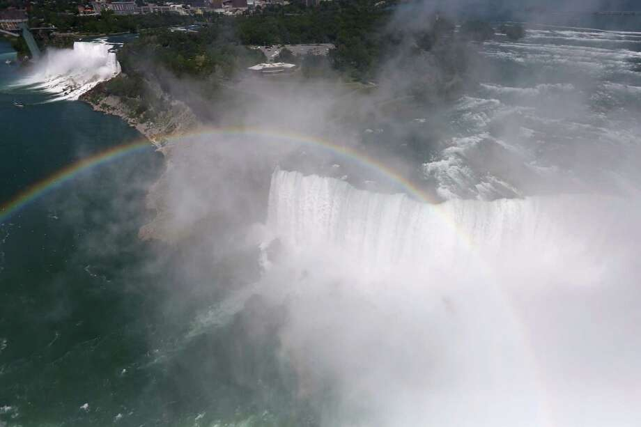 NIAGARA FALLS, NY - JUNE 04:  A rainbow is seen over the mist of Niagara Falls on June 4, 2013 in Niagara Falls, New York. The falls, which have a combined highest flow rate of any waterfalls in the world, stradle the U.S.-Canada border, drawn through the Niagara River, which drains Lake Erie into Lake Ontario. The falls, visited by millions of tourists on each side of the border, are also a major source of hydroelectric power for the region. The aerial view was seen from a helicopter flown by the U.S. Office of Air and Marine, (OAM), which monitors and patrols the U.S. Canada border. Photo: John Moore, Getty Images / 2013 Getty Images