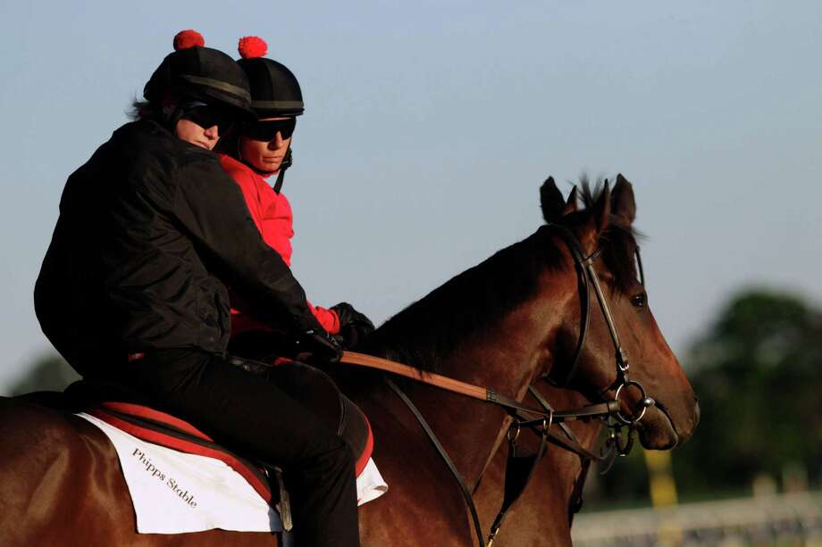 Kentucky Derby winner Orb, with exercise rider Jennifer Patterson, left, enters the track at Belmont Park for a light workout, Tuesday, June 4, 2013 in Elmont, N.Y. Orb is entered in Saturday's Belmont Stakes horse race. Photo: Mark Lennihan, AP / AP